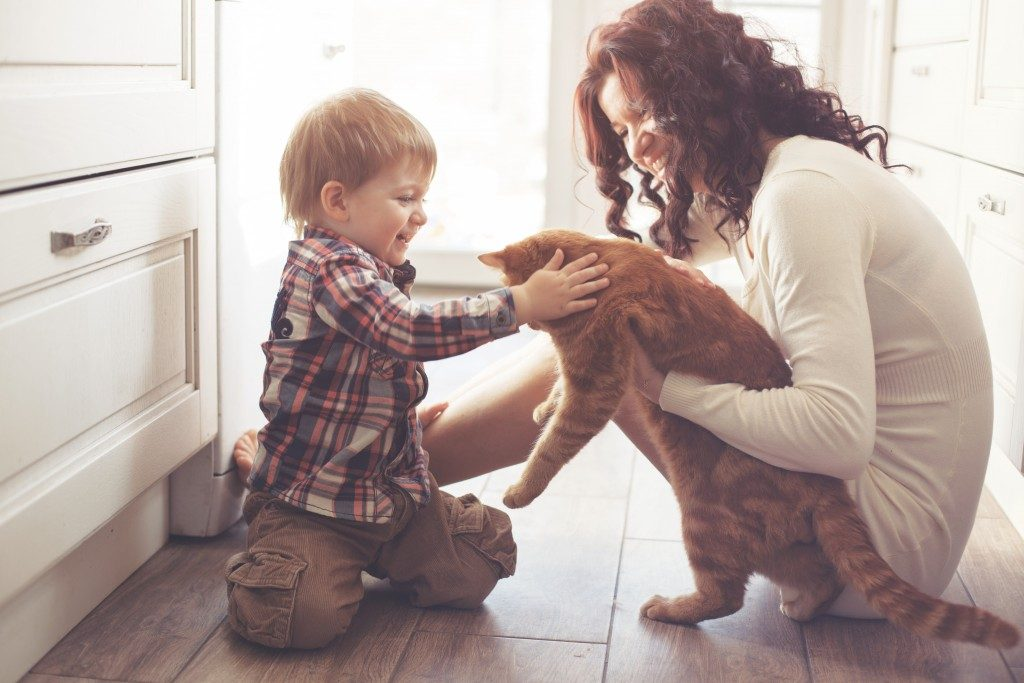 Mother with her baby playing with pet on the floor