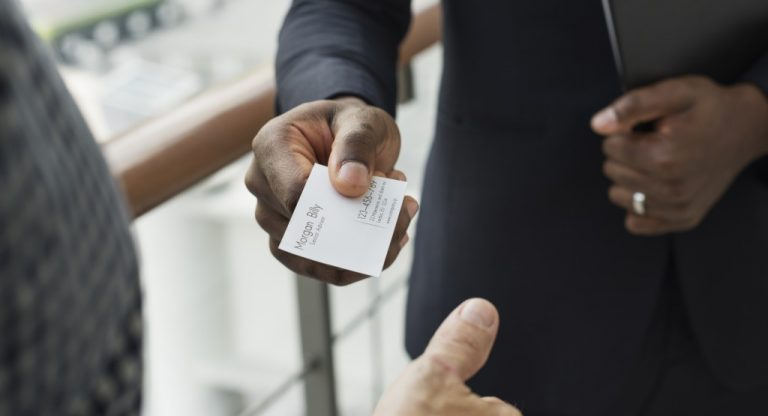 businessman giving business card to other person