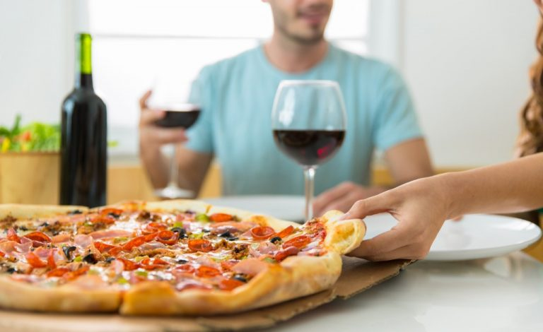 couple eating pizza and having wine at home