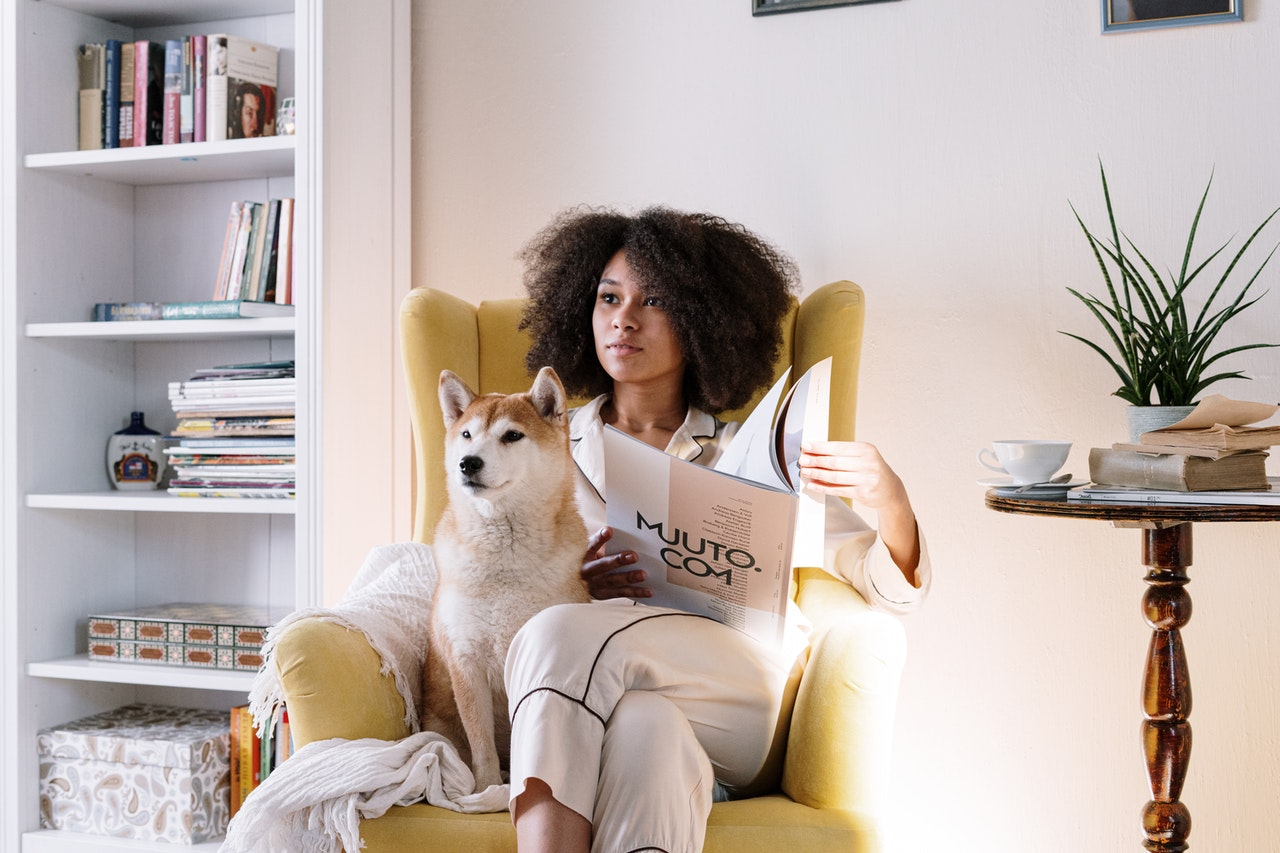 woman reading a magazine with her dog