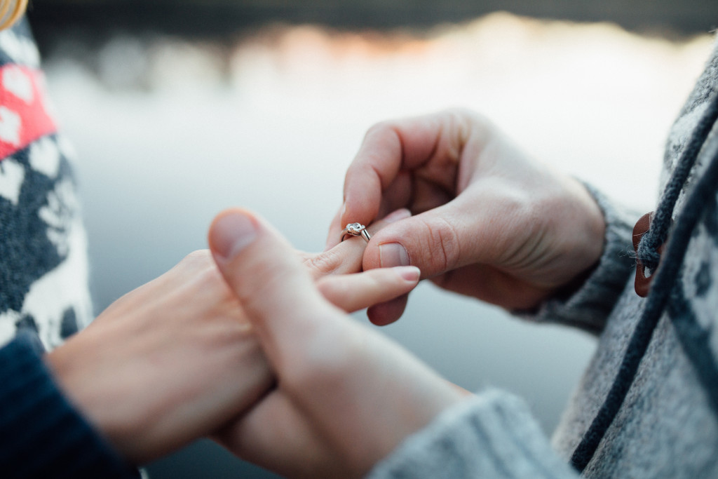 man putting ring on woman's finger